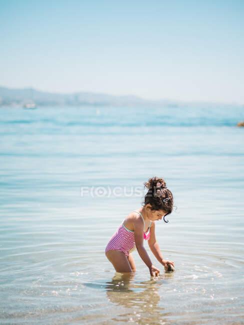 Vista lateral de adorable niña en traje de baño de pie en agua tibia de mar tranquilo - foto de stock