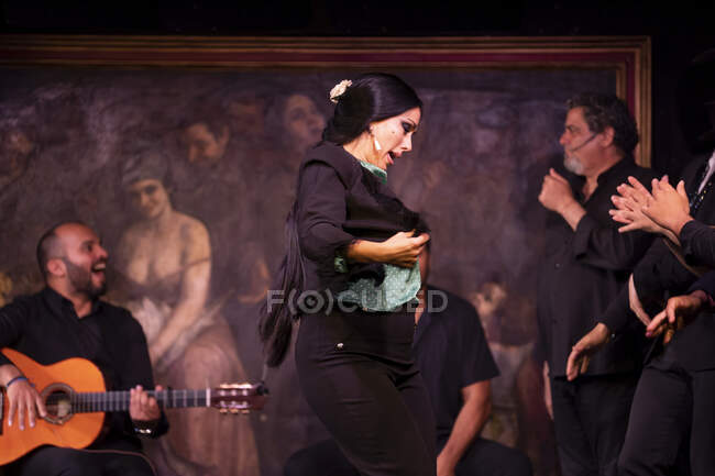 Mujer en traje negro bailando flamenco cerca de músicos masculinos hispanos durante la actuación contra la pintura en el escenario oscuro - foto de stock