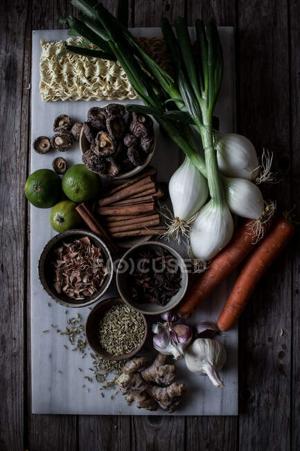From above of board with fresh vegetables and spices with dry noodles for cooking traditional Pho soup — Stock Photo