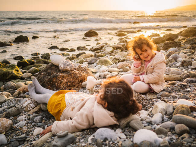 Toddler female twins playing on stony seashore on background of calm water — Stock Photo