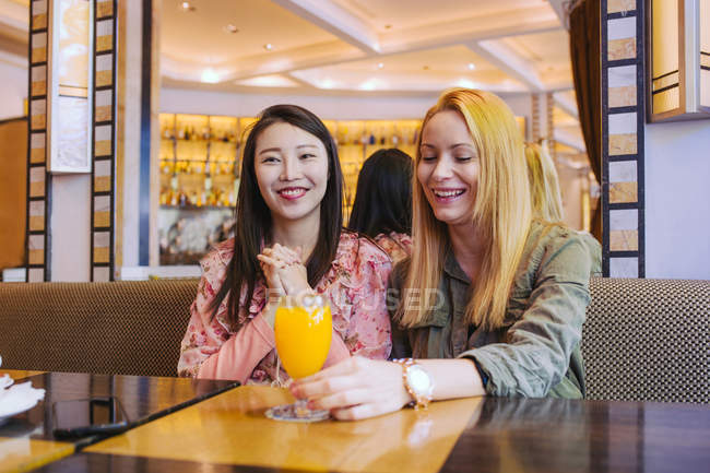 Young multiracial women smiling and speaking with each other while sitting at table in cozy cafe — Stock Photo