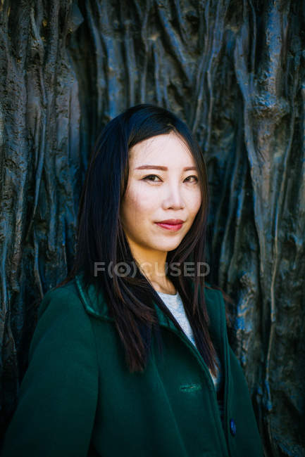 Pensive Asian woman in trendy outfit smiling and looking away while leaning on wall with relief of tree roots — Stock Photo