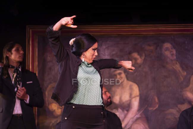 Женщина в черном костюме танцует фламенко возле латиноамериканских музыкантов во время выступления против живописи на темной сцене — стоковое фото