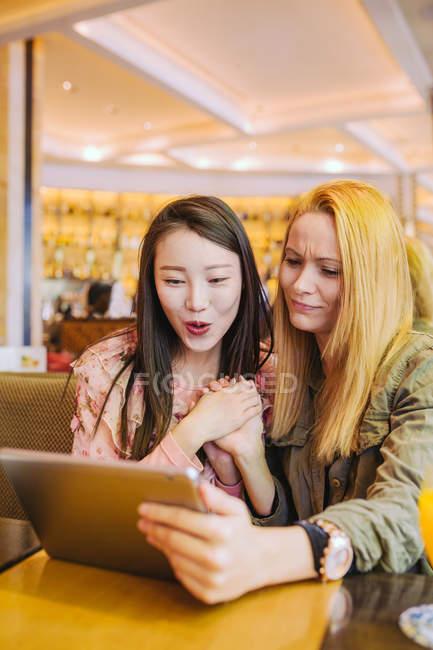 Jeune femme caucasienne montrant la vidéo sur tablette à l'ami asiatique étonné tout en étant assis à la table de café ensemble — Photo de stock