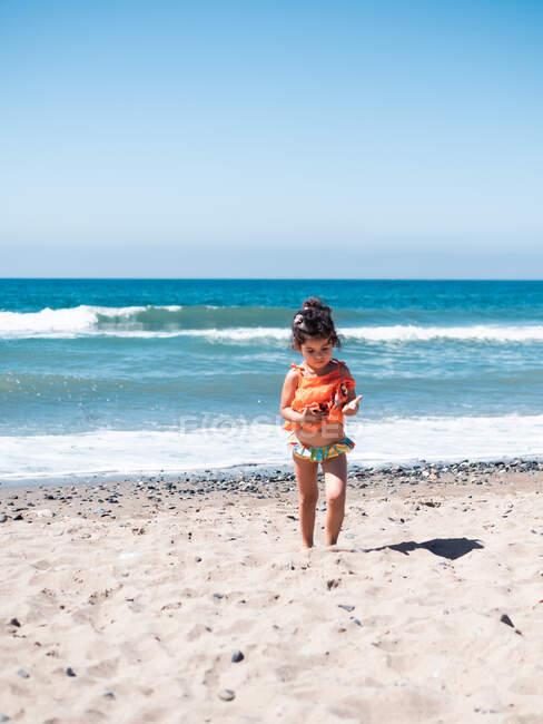 Rückansicht von kleinen Schwestern in leuchtend orangefarbenen Kleidern, die an sonnigen Tagen gemeinsam am Meer spazieren — Stockfoto