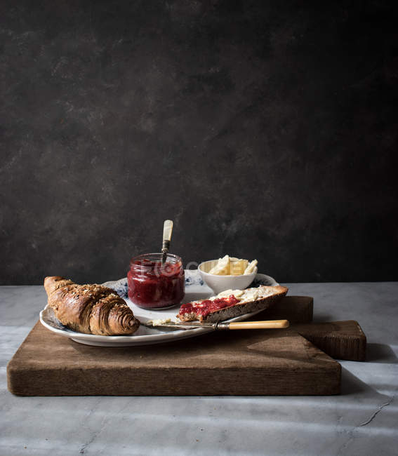 Crispy croissant with toast, butter and strawberry marmalade served on plate on wooden board — Stock Photo