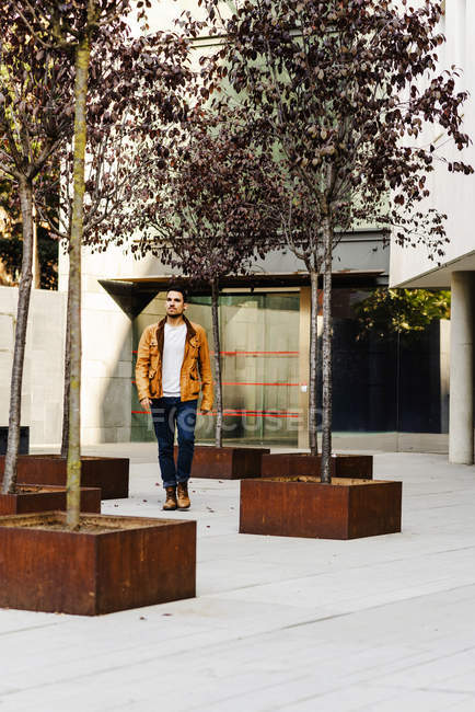 Trendy man in casual outfit looking away while walking outside modern building — Stock Photo
