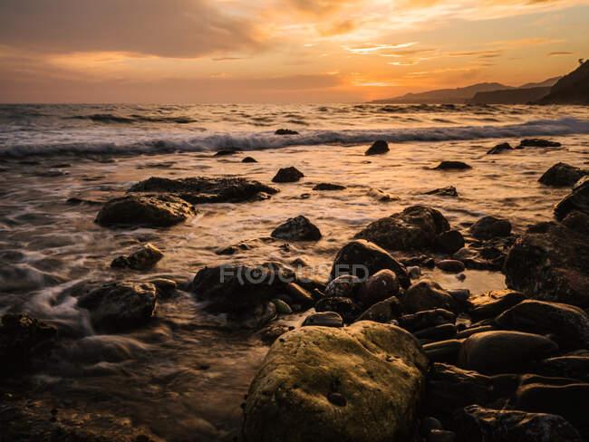 Неповторний вид мокрих каменів на спокійному морі проти сонячного неба. — стокове фото
