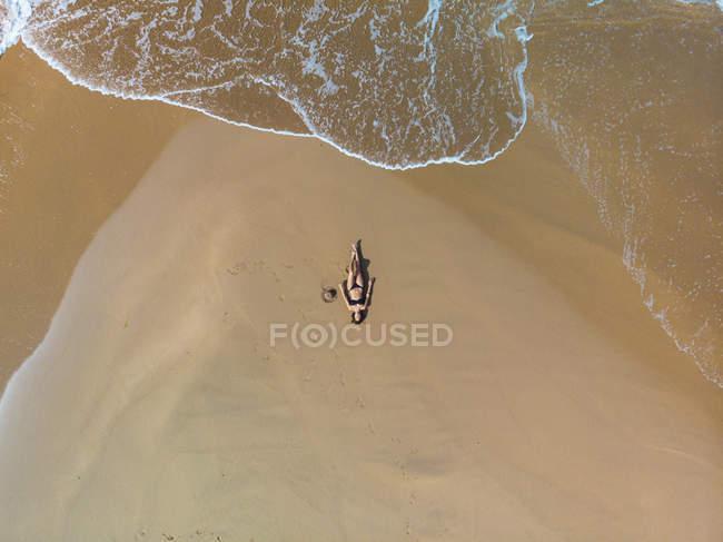 Mulher relaxed magro no biquini que encontra-se na praia arenosa — Fotografia de Stock
