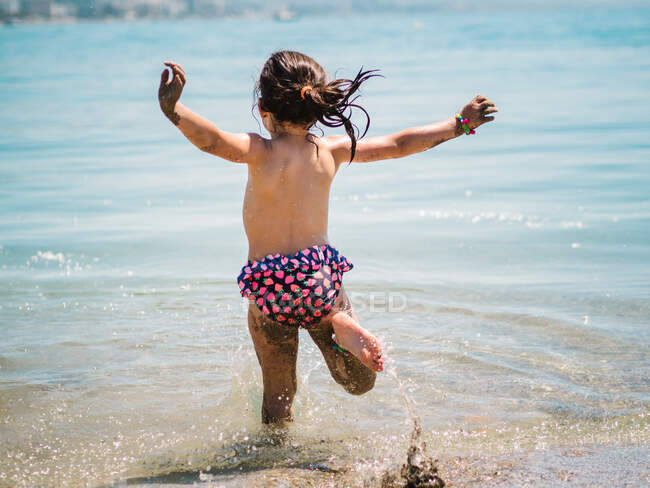 Back view of anonymous joyful cute girl playing in water of sea on background of calm seashore — Stock Photo