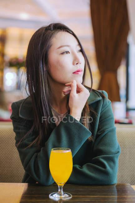 Задумлива азіатка в стильному зеленому пальто, озираючись, сидячи за столом у кафе зі склянкою свіжого соку. — стокове фото