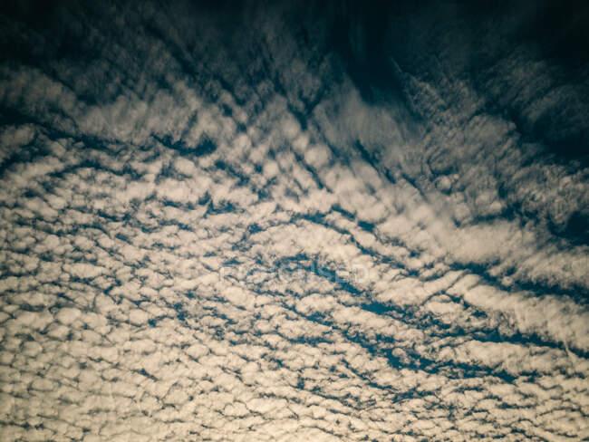 Fond lumineux d'un beau ciel calme avec des nuages de cirrus au coucher du soleil — Photo de stock