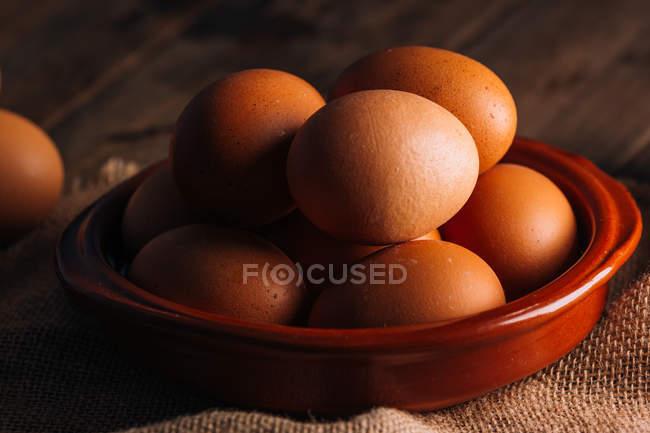 Куриные яйца в миску на деревянный стол — стоковое фото