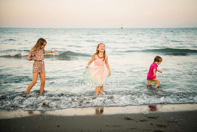 Gruppe kleiner Junge mit zwei Schwestern spielt in seichtem Wasser an der Küste — Stockfoto