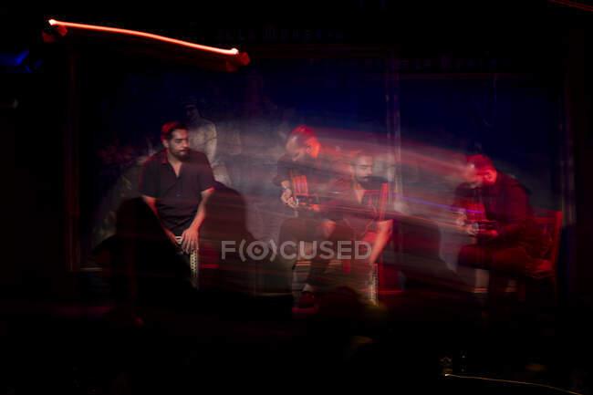 Hombres hispanos tocando percusión y guitarra acústica durante actuación flamenca en escenario oscuro - foto de stock
