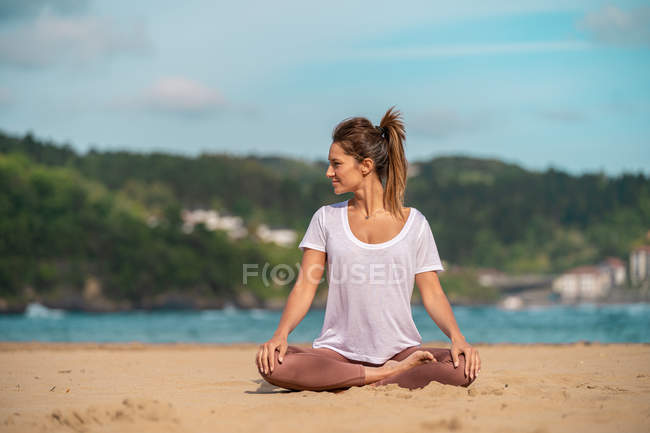 Young female practicing yoga on sandy beach — Stock Photo