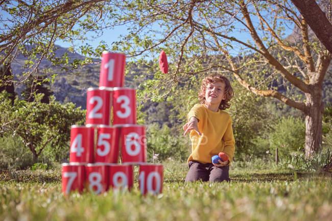 Criança alegre ajoelhado e jogando bolas em pirâmide de latas vermelhas no fundo da natureza — Fotografia de Stock