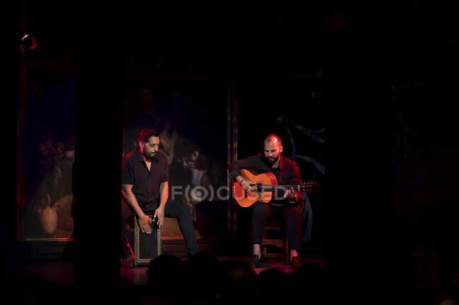Испанские мужчины играют на ударных и акустической гитаре во время выступления фламенко на темной сцене — стоковое фото