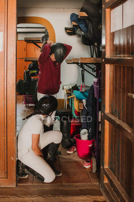Side view of women in closet with staff getting dressed for horse riding — Stock Photo