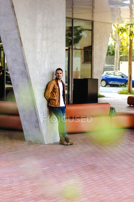 Confident trendy young guy leaning on concrete pillar near leather couch outside contemporary building on city street — Foto stock