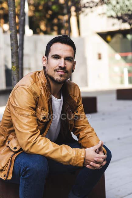 Уверенный модный молодой парень, сидящий на улице — стоковое фото
