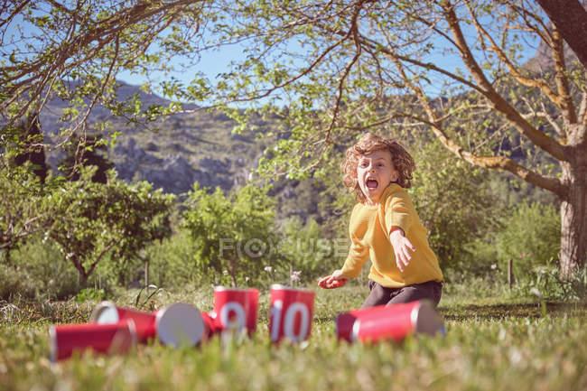 Jovem alegre ajoelhado e jogando bola na pirâmide de latas vermelhas no fundo da natureza — Fotografia de Stock