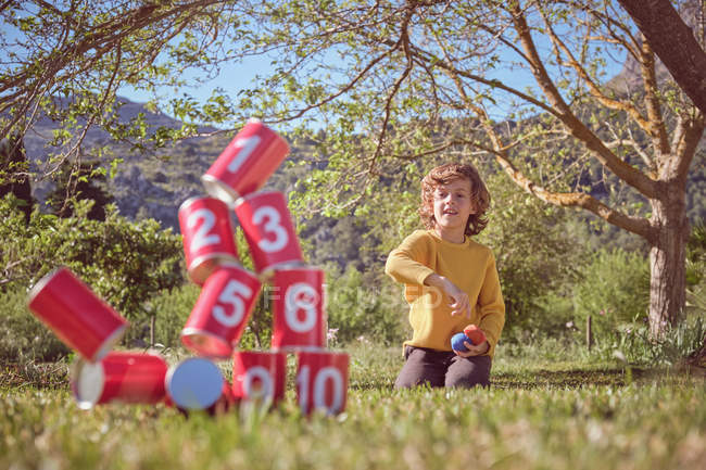 Cheerful kid kneeling and throwing balls in pyramid of red tin cans on nature background — Stock Photo