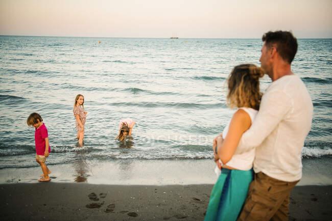 Seitenansicht der Umarmung von Mann und Frau mit Blick auf verspielte Jungen und Mädchen im Wasser an der Küste — Stockfoto