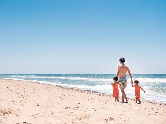 Vista posteriore dell'uomo che cammina lungo il mare con le bambine sullo sfondo del mare calmo e del cielo blu — Foto stock