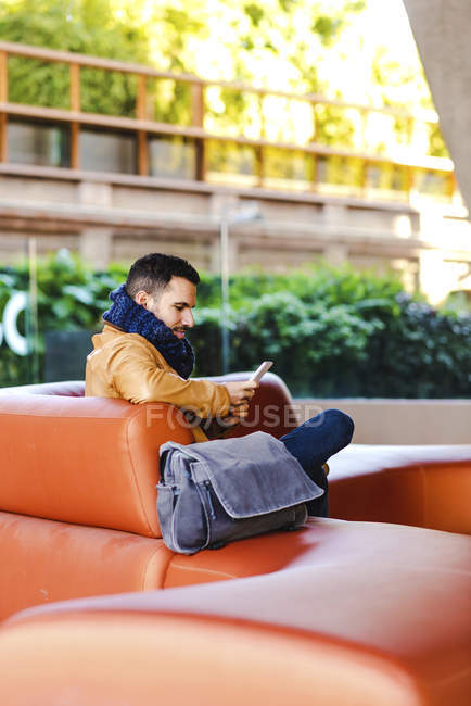 Young man in trendy outfit browsing smartphone while sitting on comfortable leather sofa - foto de stock