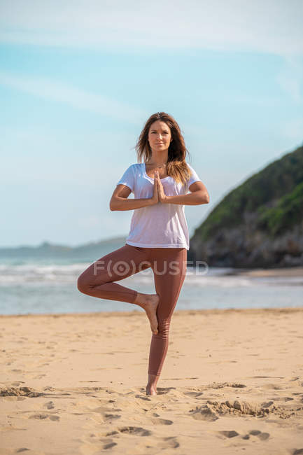 Young woman practicing yoga on sandy beach — Stock Photo