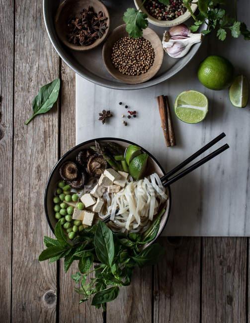 Суп Фо с лапшой на мраморной доске на деревянном столе со специями — стоковое фото