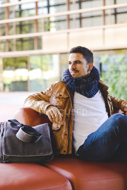 Man in trendy outfit sitting on comfortable red leather couch in modern building — Stock Photo