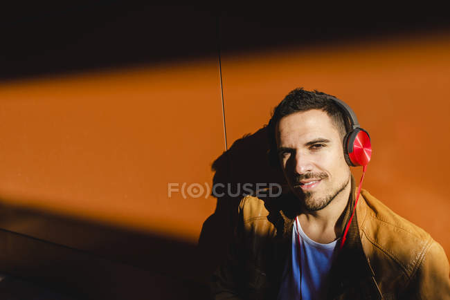Positive young man in stylish outfit with headphones listening to music near wall with shadow — Stock Photo