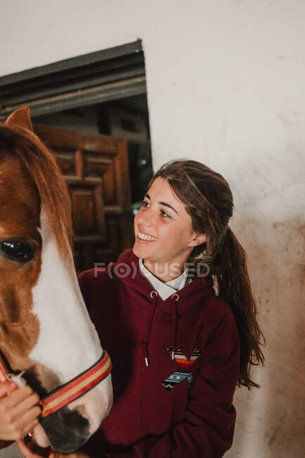 Teenage girl embracing with small pony in cute hat on ears standing inside of stable — Stock Photo