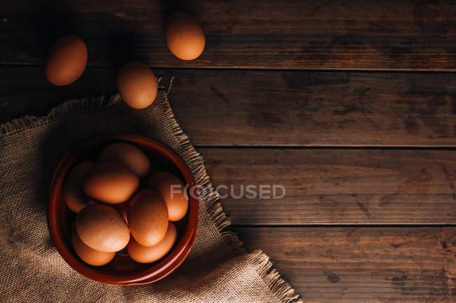 Œufs de poulet avec bol et sac sur table en bois — Photo de stock