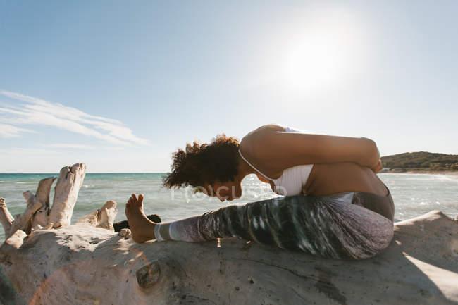 Афроамериканка, занимающаяся йогой на пляже — стоковое фото