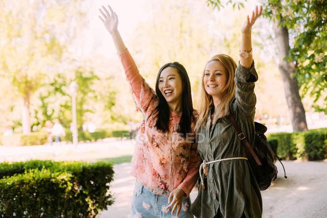 Excited multiracial females pointing and waving hand while standing on park alley on sunny day — Stock Photo
