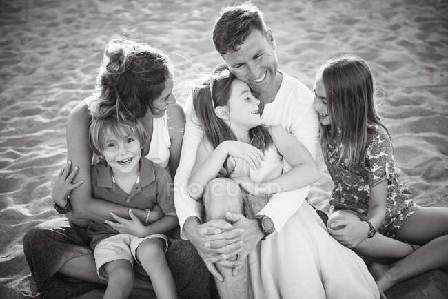 Adult loving man and woman with cheerful son and daughters sitting together looking at each other, black and white photo — Stock Photo