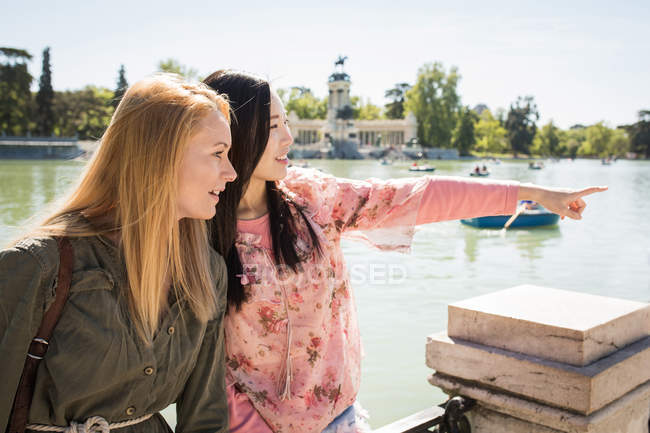 Multiethnic young women laughing and looking away while sitting on railing and pointing with finger near river — Stock Photo
