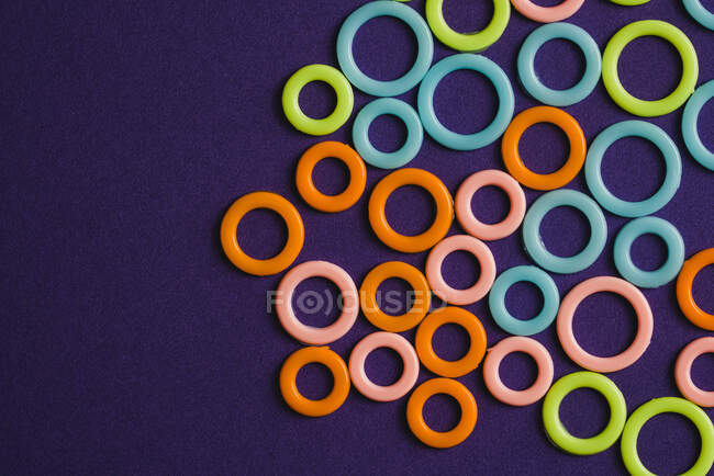 De arriba brillante naranja rosa azul anillos verdes de diferentes tamaños sobre fondo púrpura - foto de stock