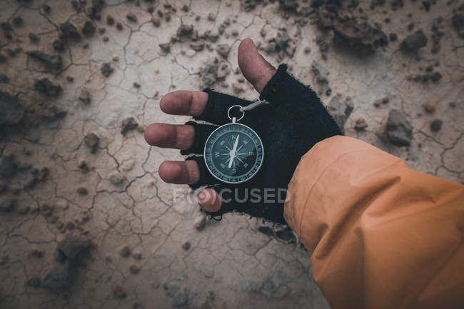 Closeup of hand in black fingerless glove holding compass on desert place — Stock Photo