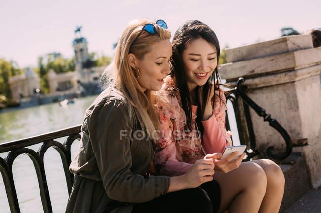Jeunes femmes multiraciales dans des tenues à la mode souriant et naviguant smartphone tout en étant assis près de remblai balustrade par une journée ensoleillée sur la rue de la ville — Photo de stock