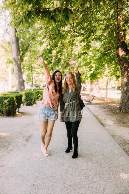 Взволнованные многорасовые женщины показывали и махали руками, стоя в парке в солнечный день — стоковое фото