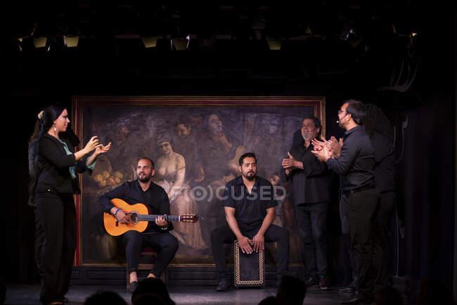 Hispanische Männer mit Percussion und Akustikgitarre während eines Flamenco-Auftritts auf der dunklen Bühne — Stockfoto