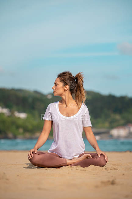 Молодая женщина практикует йогу на песчаном пляже — стоковое фото