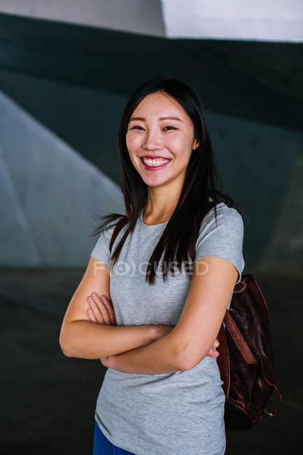 Взволнованная азиатская женщина в повседневном наряде, держащая руки скрещенными и весело улыбающаяся на камеру — стоковое фото