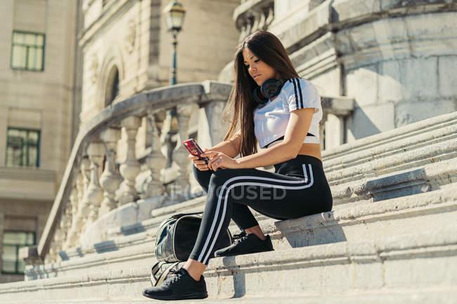 Jovem mulher atraente em sportswear mensagens com smartphone sentado em escadas de pedra — Fotografia de Stock