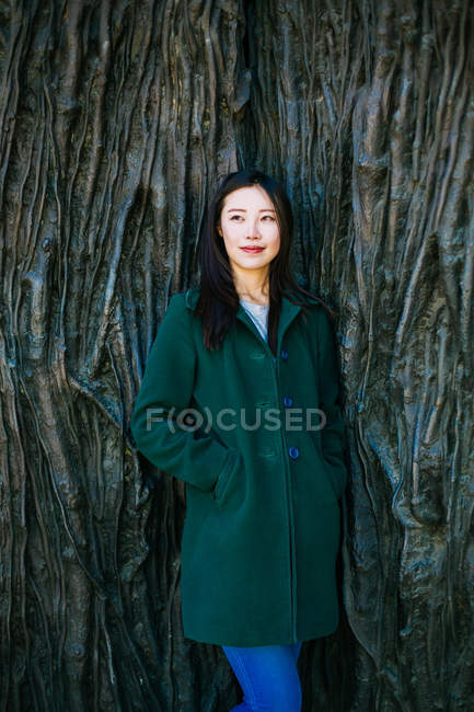 Pensive Asian woman in trendy outfit looking away while leaning on wall with relief of tree roots — Stock Photo