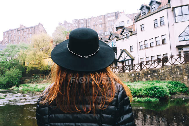 Back view of woman in hat contemplating landscape of old masonry buildings with shallow river flowing among green bushes, Scotland — Stock Photo